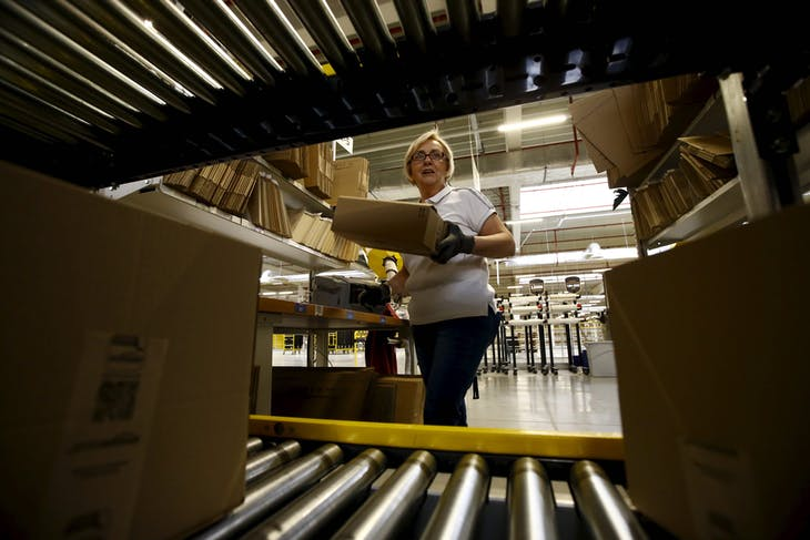 Worker packs products at an Amazon Fulfilment Center in Wroclaw