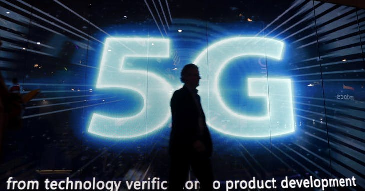 A_visitors_walks_past_a_5G_sign_during_M